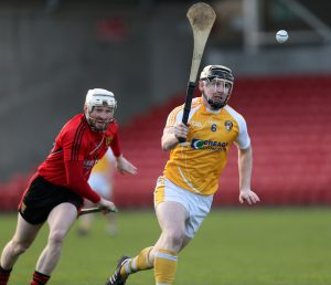 Antrim centre back Neal McAuley wins possession ahead of Down's Conor O'Prey